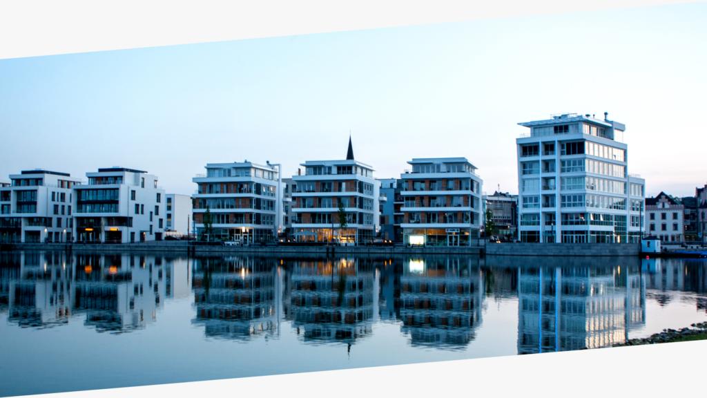Wohnsiedlung vor blauem Himmel und Wasser
